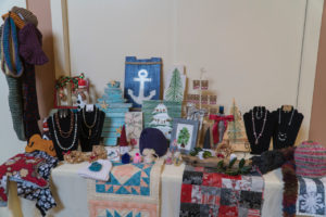 Display of palate art, jewelry, knitted items, seaglass Christmas tree, ornaments, and home decor items