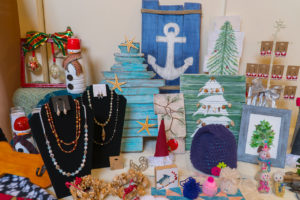 Display of palate art, jewelry, knited items, seaglass Christmas tree, ornaments, and home decor items